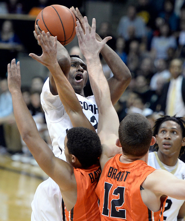 . Colorado\'s Jaron Hopkins takes a shot over a swarm of defenders including Angus Brandt, No. 12, during an NCAA game against Oregon State on Thursday, Jan. 2, at the Coors Event Center in Boulder.  Jeremy Papasso/ Camera