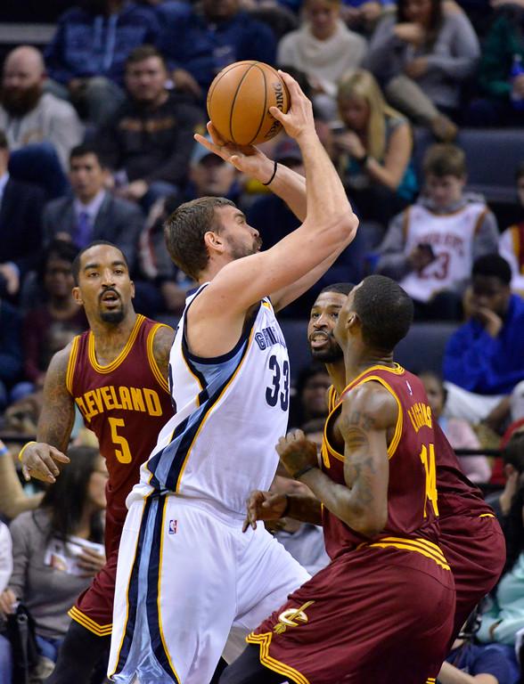. Memphis Grizzlies center Marc Gasol (33) shoots between Cleveland Cavaliers guard J.R. Smith (5), from left, center Tristan Thompson (13), and guard DeAndre Liggins (14) in the first half of an NBA basketball game Wednesday, Dec. 14, 2016, in Memphis, Tenn. (AP Photo/Brandon Dill)