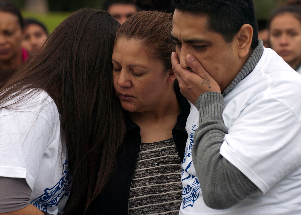 """. ON08-BIKERIDE-01-JCM (Jennifer Cappuccio Maher/Staff Photographer) Ivan Arturo Aguilar\'s sister Alix, left, mother Argelia and father Raul mourn as friends and family gather to remember the Cal Poly student Thursday, March 7, 2013, at Cal Poly Pomona in Pomona. A \""""ghost bike\"""" was installed and a memorial bike ride was held in his memory. Aguilar was killed after he was hit by a car while riding his bike on campus last week."""
