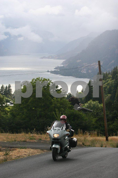 A biker tops over a rise in White Salmon, Washington with the Columbia River in the background.