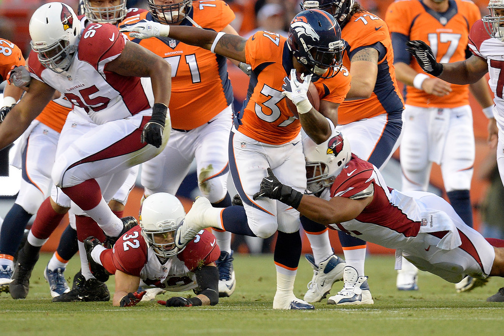 . Denver Broncos running back Jeremiah Johnson (37) runs through attempted tackles by Arizona Cardinals defensive back Tyrann Mathieu (32) and linebacker Kevin Minter (51) during the first half on August 29, 2013 at Sports Authority Field at Mile High. The Denver Broncos hosted the Arizona Cardinals in the final game of the preseason. (Photo by John Leyba/The Denver Post)