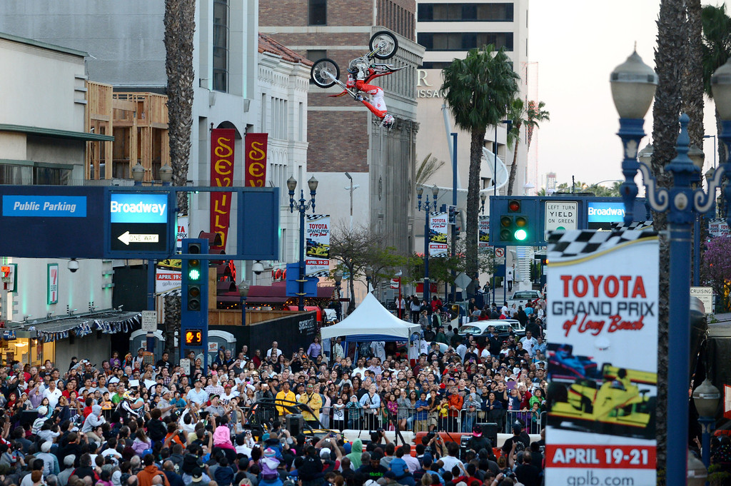 . Long Beach, Calif., -- 04-18-13- A stunt motorcycle does a backflip along Broadway and Pine Ave. during the  Tecate Light Thunder Thursday On Pine .  Race fans were able to get a close up look at race cars, meet drivers and see and IndyCar pit demonstration.   Stephen Carr/  Los Angeles Newspaper Group