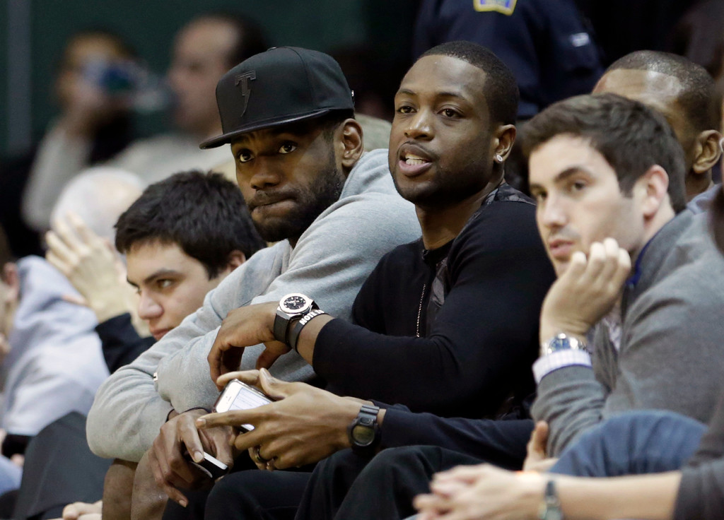 . Miami Heat\'s LeBron James, left, and Dwyane Wade watch the NCAA basketball game between Duke and Miami during the second half of an NCAA basketball game in Coral Gables, Fla., Wednesday, Jan. 22, 2014. duke won 67-46. (AP Photo/Alan Diaz)