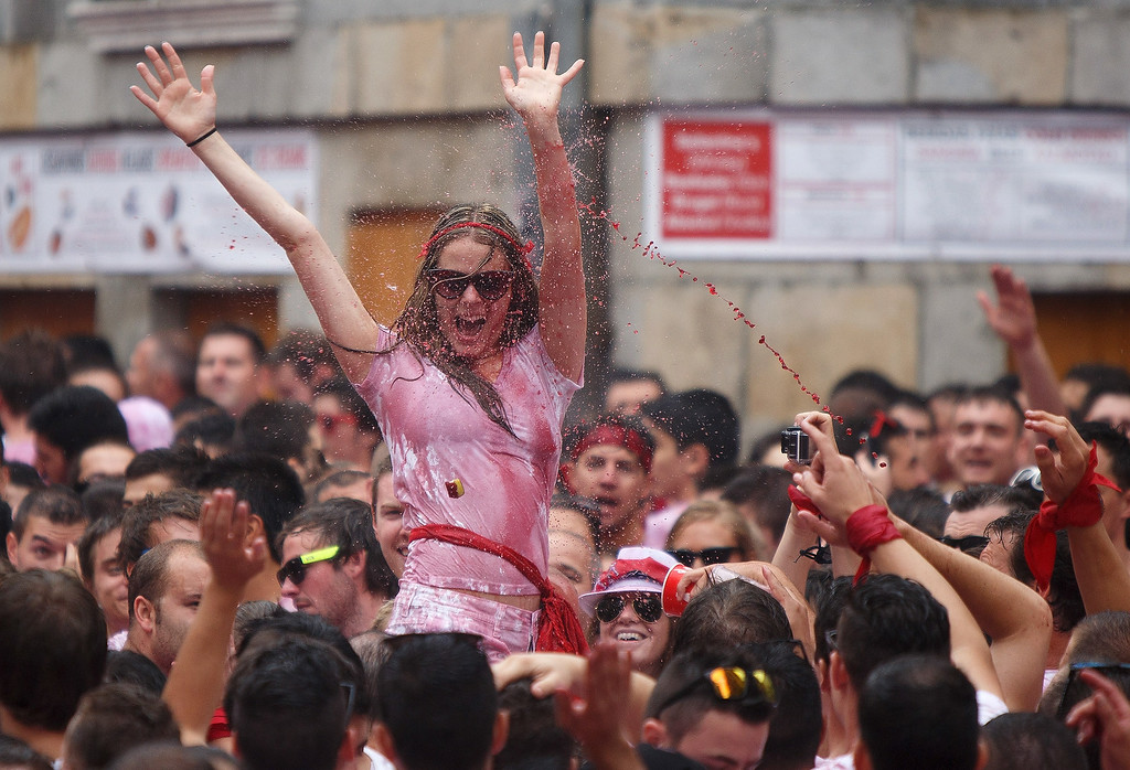 . Revellers cheer and throw red wine during the opening and the firing of the \'Chupinazo\' rocket which starts the 2014 Festival of the San Fermin Running of the Bulls on July 6, 2014 in Pamplona, Spain. The annual Fiesta de San Fermin, made famous by the 1926 novel of US writer Ernest Hemmingway entitled \'The Sun Also Rises\', involves the daily running of the bulls through the historic heart of Pamplona to the bull ring.  (Photo by Pablo Blazquez Dominguez/Getty Images)