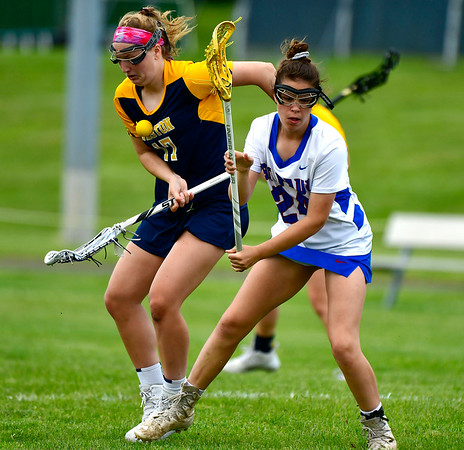 5/29/2019 Mike Orazzi | Staff St. Paul's Cameron Baston (24)nd Weston's Becca Strouch (17) during Wednesday's Class S First Round lacrosse match in Bristol.