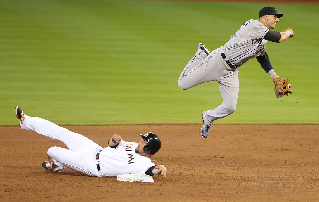 . Shortstop Troy Tulowitzki #2 of the Colorado Rockies cannot turn a double play against Casey McGehee #9 of the Colorado Rockies during the first inning at Marlins Park on April 3, 2014 in Miami, Florida.  (Photo by Marc Serota/Getty Images)