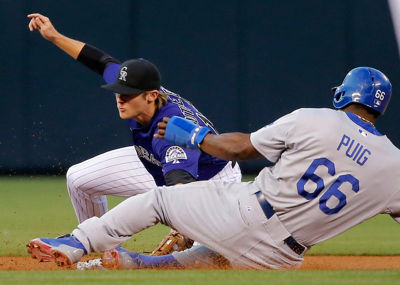 . Los Angeles Dodgers\' Yasiel Puig (66) is safe at second as Colorado Rockies shortstop Josh Rutledge (14) applies the late tag during the first inning of a baseball game Monday, Sept. 15, 2014, in Denver. (AP Photo/Jack Dempsey)