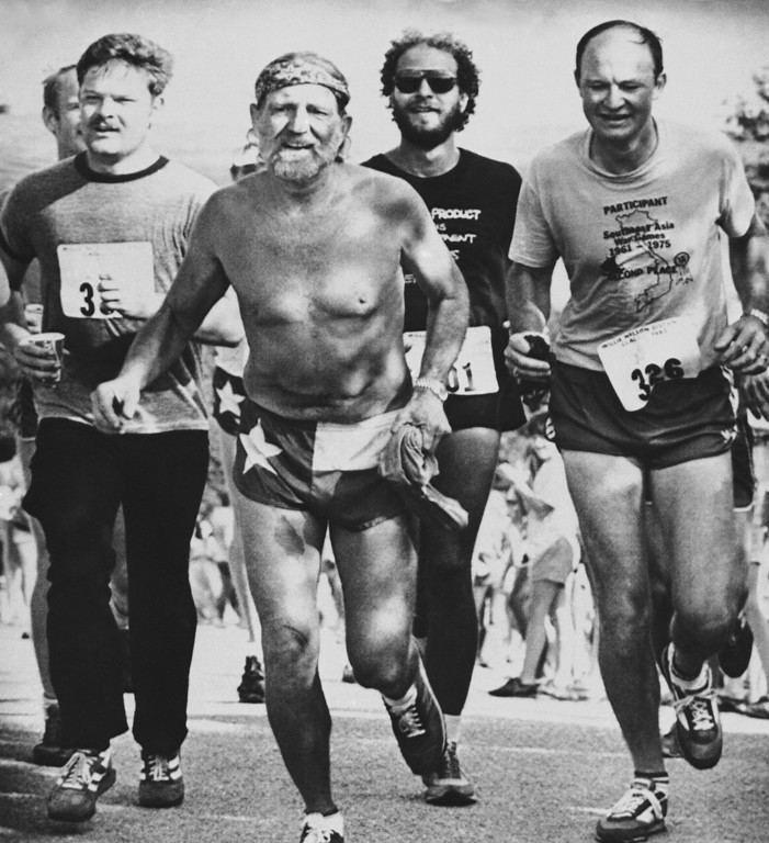 . Country singer Willie Nelson second from left, crosses the finish line at the first annual Willie Nelson distance classic on Sunday, June 15, 1980 at the Pedernales Country Clute owns near Lake Travis in Austin, Texas. Nelson finished the hilly, 6.2 mile course one hour, 7 minutes and 45 seconds. More than 1,000 runners competed. (AP Photo/Daemmrich)