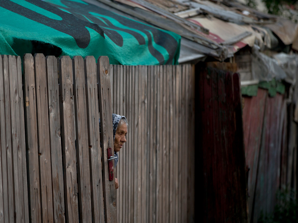 . A Roma woman peers from behind a fence whilst she and more than 100 people are evicted from the homes they lived in, in Bucharest, Romania, Monday, Sept. 15, 2014. (AP Photo/Vadim Ghirda)