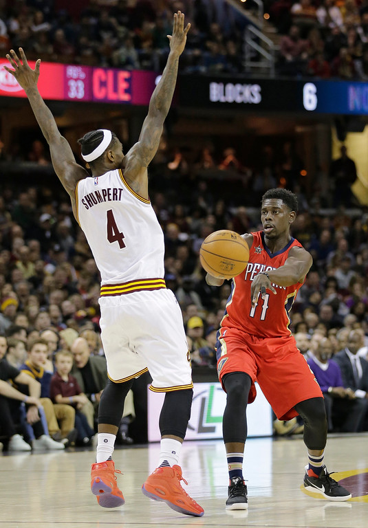 . New Orleans Pelicans\' Jrue Holiday (11) passes against Cleveland Cavaliers\' Iman Shumpert (4) in the second half of an NBA basketball game, Monday, Jan. 2, 2017, in Cleveland. The Cavaliers won 90-82. (AP Photo/Tony Dejak)