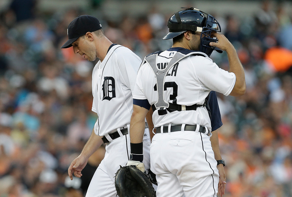 . Detroit Tigers pitcher Max Scherzer leaves the mound after being relieved as Alex Avila (13) looks on against the Kansas City Royals in the fifth inning of a baseball game in Detroit, Tuesday, June 17, 2014.  (AP Photo/Paul Sancya)