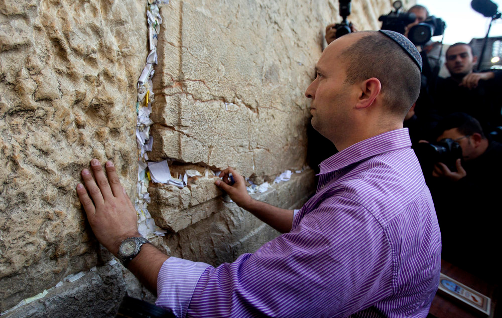 Description of . Naftali Bennett, head of the Jewish Home party, touches the stones of the Western Wall, the holiest site where Jews can pray, in Jerusalem's old city, Monday, Jan. 21, 2013. General elections in Israel will be held Tuesday, Jan. 22, 2013. (AP Photo/Sebastian Scheiner)