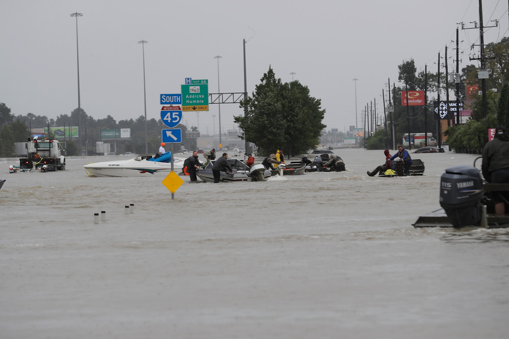 . Volunteer rescue boats make their way into a flooded subdivision to rescue stranded residents as floodwaters from Tropical Storm Harvey rise Monday, Aug. 28, 2017, in Spring, Texas. (AP Photo/David J. Phillip)