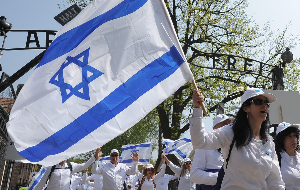""". A woman waves an Israeli flag as she walks through the gate with the inscription  \""""Arbeit Macht Frei\""""  in the Auschwitz-Birkenau German Nazi Death Camp at the start of the yearly March of the Living,  in Oswiecim, Poland, Thursday, May 5, 2016. (AP Photo/Alik Keplicz)"""