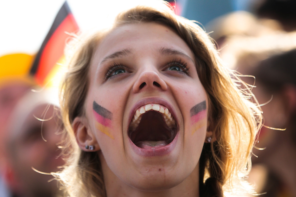 . A German soccer fan celebrates their team\'s third goal during their first game at the World Cup 2014 at a public viewing zone called \'fan mile\' in Berlin, Monday, June 16, 2014. Germany plays against Portugal in group G match at the soccer World Cup 2014 in Brazil. (AP Photo/Markus Schreiber)