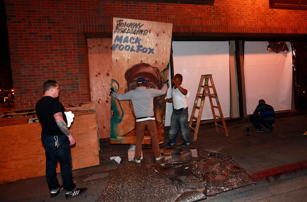 . Volunteers cover up windows broken during a Trayvon Martin protest when it marched past the non-profit Youth Radio offices on 17th Street at Broadway in Oakland, Calif., early Tuesday morning, July 17, 2013.  (Karl Mondon/Bay Area News Group)