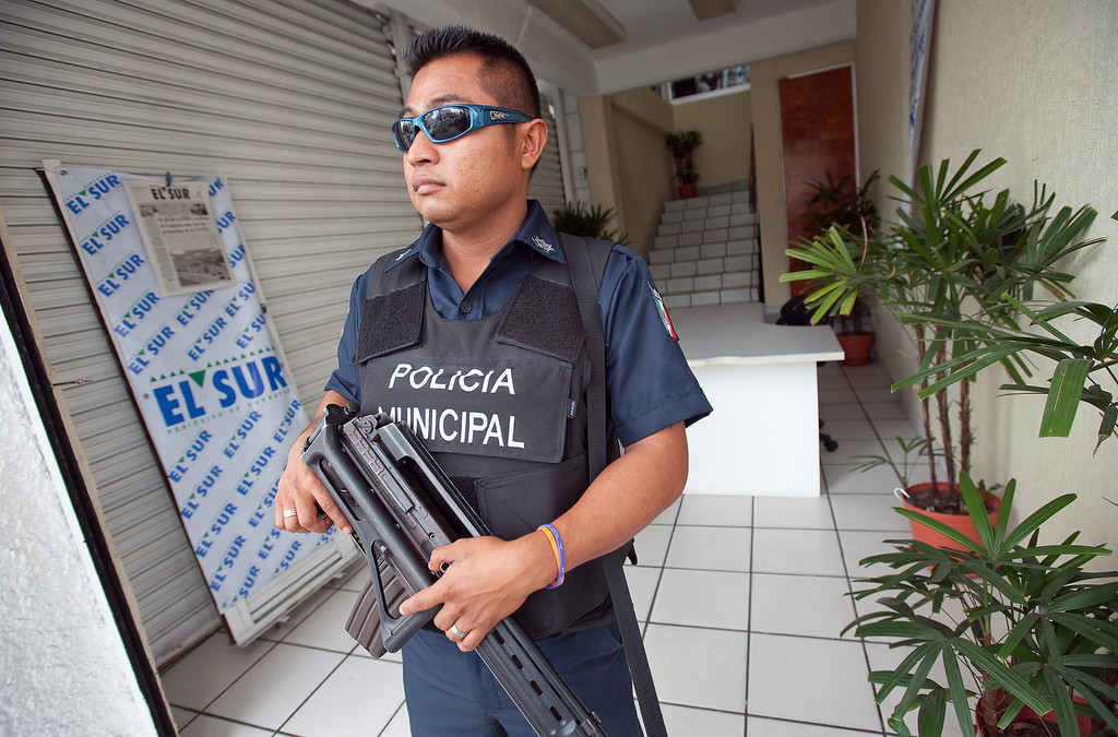 . Mexican journalists are under siege throughout the country both from organized crime and abusive government authorities. Reporters and photographers at El Sur newspaper in Acapulco, take various precautions to deal with the threats they receive. To protect journalists during working hours, Acapulco municipal policeman, Juan Hernandez Dorantes, 30, guards the entrance to the El Sur newspapers offices from 8 am until 8 pm, each day of the week. (Keith Dannemiller/MCT)
