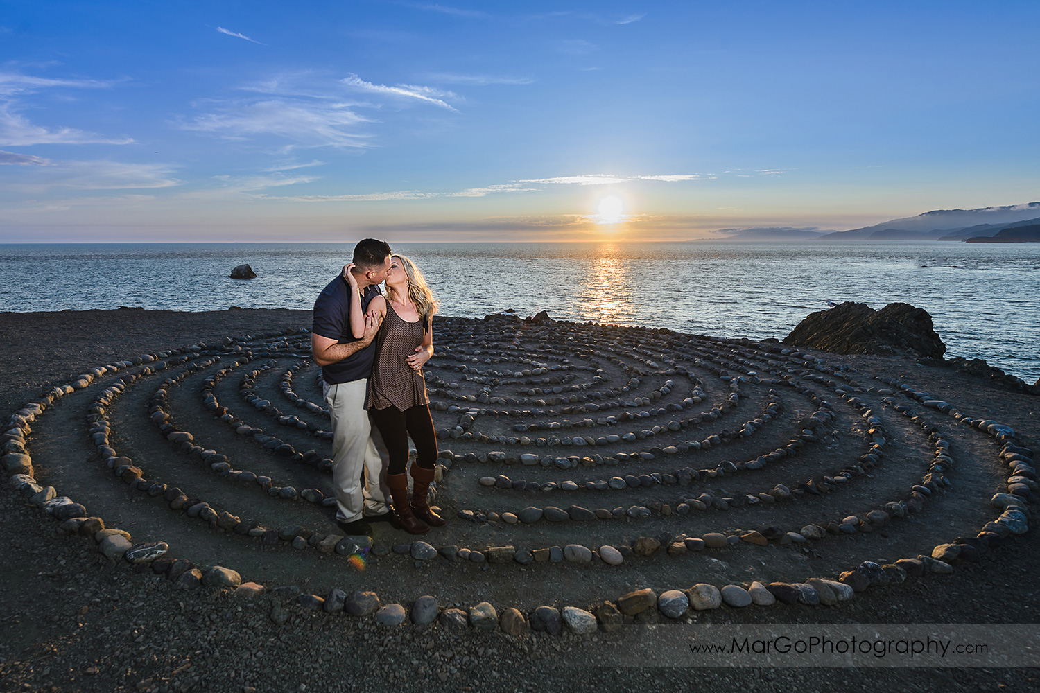 man in navy blue shirt and woman in brown tunic kissing in the stone labyrinth during engagement session at San Francisco Lands End
