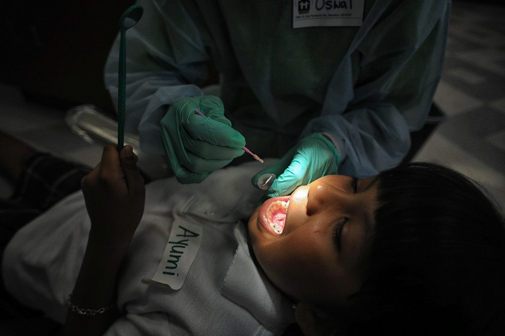 . Dr. Punita Oswal gives Ayumi Guadama, 8-years-old, a visual dental examine and fluoride treatment during MEND�s (Meet Each Need with Dignity) 13th annual �Head to Toes,� program at the Pacoima charity�s center Wednesday, August 27, 2014. 240 third-graders from Pacoima�s Vaughn Next Century Learning Center were provided with full back-to-school care: free dental and vision screenings through a healthcare initiative with Verizon Foundation, new shoes and new backpacks chock-full of school supplies school supplies donated by the Ella Fitzgerald Charitable Foundation. (Photo by Hans Gutknecht/Los Angeles Daily News)