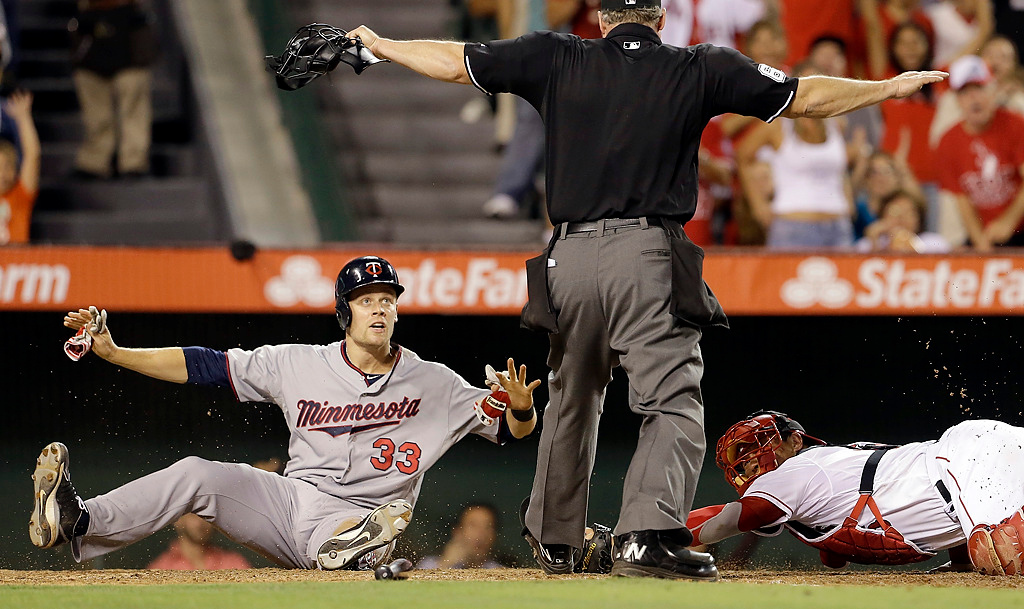. The Twins\' Justin Morneau scores on a Ryan Doumit double as Los Angeles Angels catcher Hank Conger misses the tag and plate umpire Ted Barrett signals \'safe\' in the eighth inning of their game in Anaheim, Calif., Tuesday, July 23, 2013. (AP Photo/Reed Saxon)