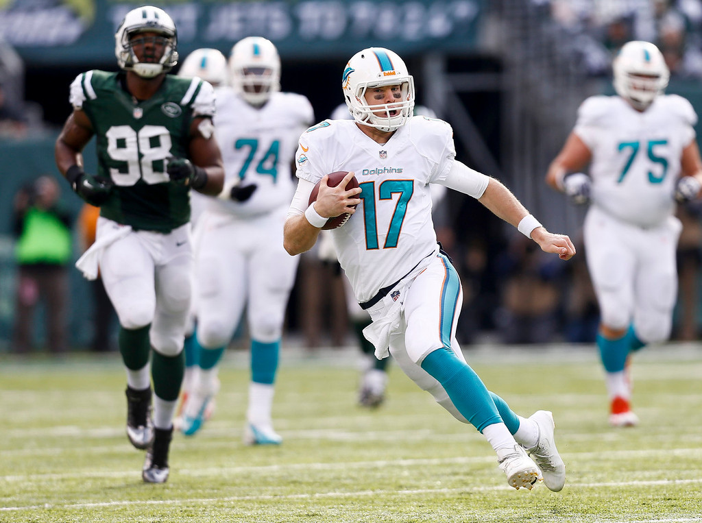 . Ryan Tannehill #17 of the Miami Dolphins runs for a first down against the New York Jets during their game at MetLife Stadium on December 1, 2013 in East Rutherford, New Jersey.  (Photo by Jeff Zelevansky/Getty Images)