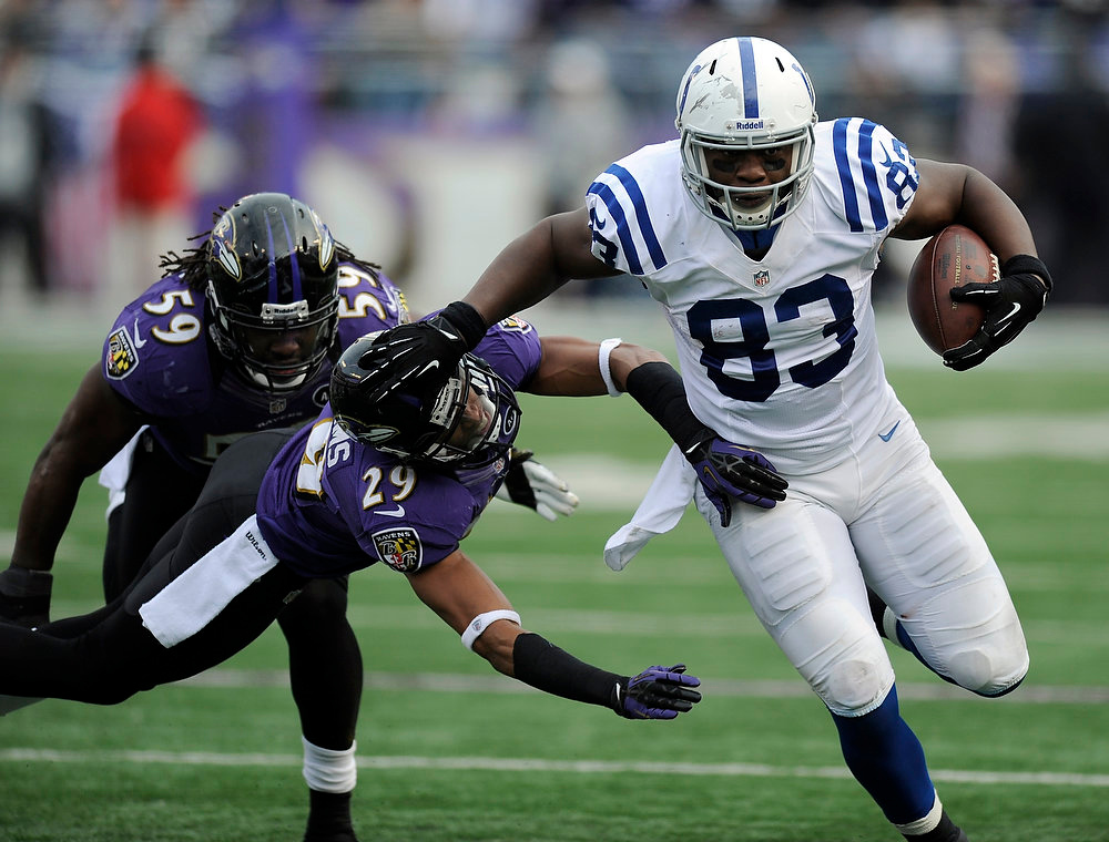 Description of . Indianapolis Colts tight end Dwayne Allen (83) tries to get away from Baltimore Ravens inside linebacker Dannell Ellerbe (59) and cornerback Cary Williams (29) during the first half of an NFL wild card playoff football game Sunday, Jan. 6, 2013, in Baltimore. (AP Photo/Nick Wass)