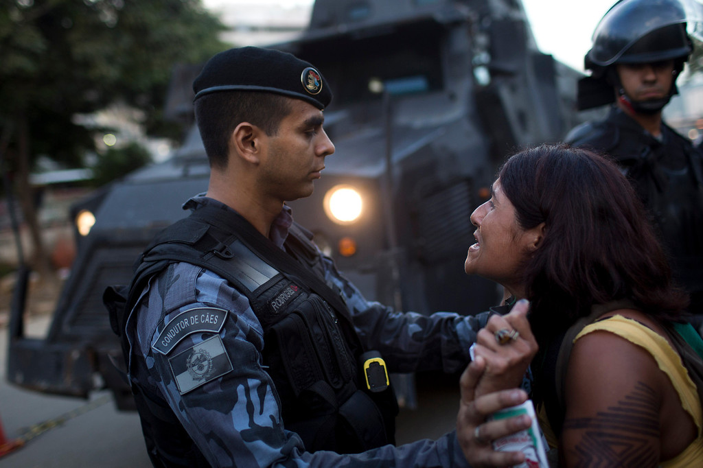 . A supporter of the indigenous people who have been occupying the old Indian Museum is held by police as she protests outside the old Indian Museum in Rio de Janeiro, Friday, March 22, 2013. The clash Friday is a bid to expel the group, some of whom have been squatting in the crumbling complex for years. The Indian museum has been at the center of a drawn-out legal battle between the several dozen Indians who\'ve been living there for years and state and local authorities. Officials initially wanted to raze the complex as part of renovations ahead of Brazil\'s 2014 World Cup. (AP Photo/Felipe Dana)