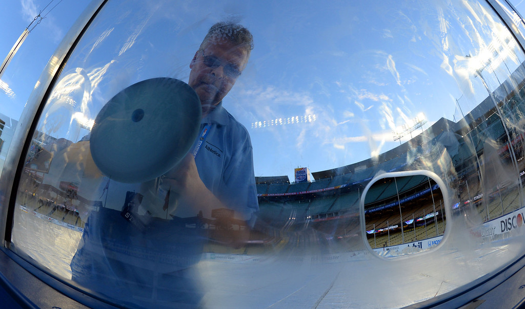 . Bruce Irving of the NHL ice crew buffs the glass prior to the start of the inaugural NHL Stadium Series game at Dodger Stadium in Los Angeles on Saturday, Jan. 25, 2014. (Keith Birmingham Pasadena Star-News)