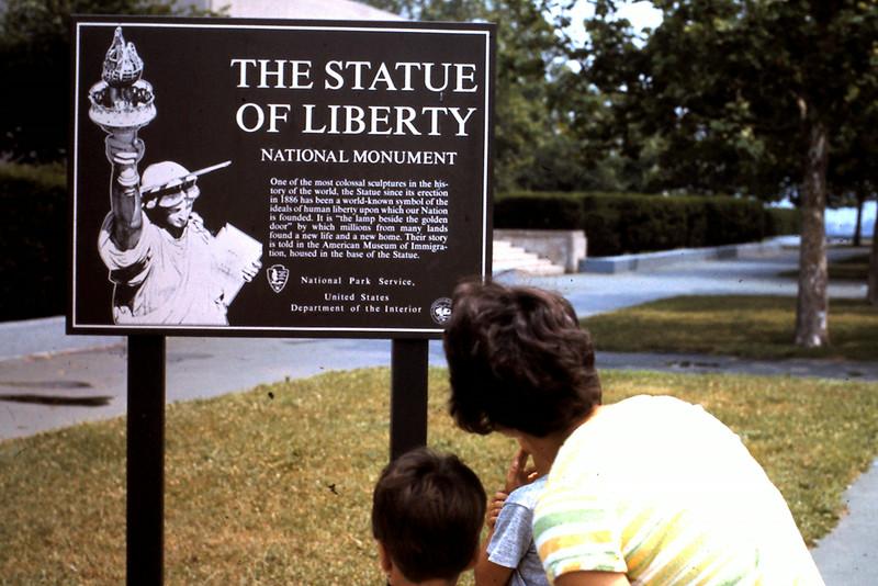 Jo, Jeff, Randy at Statue of Liberty sign