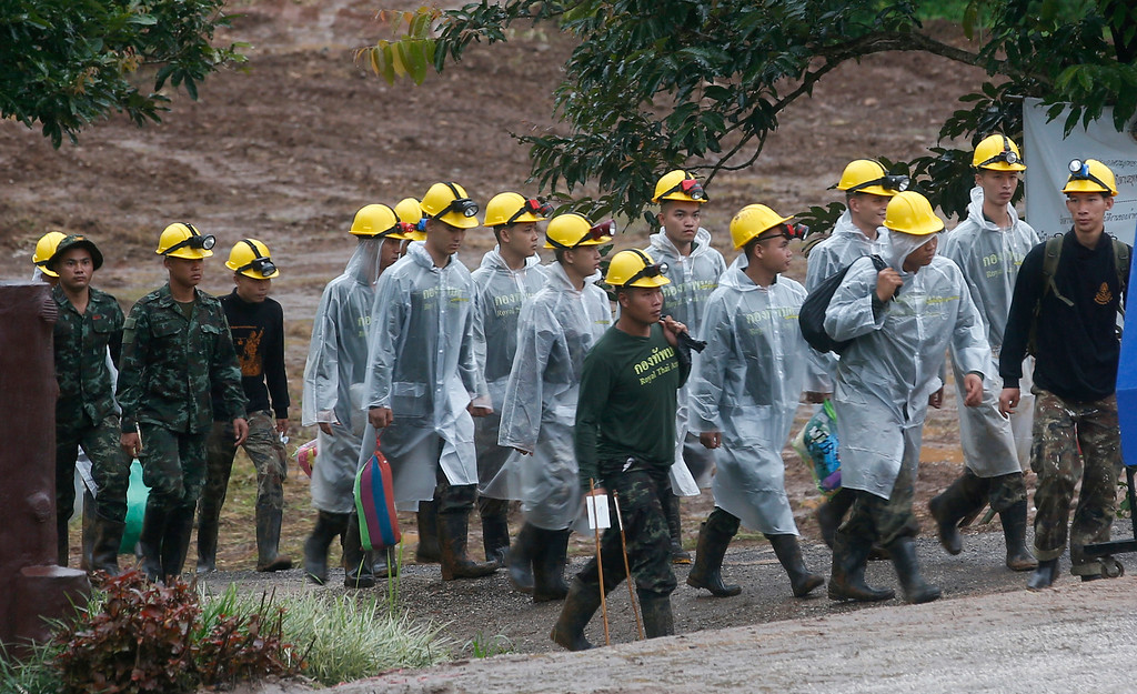 . Rescuers walk toward the entrance to a cave complex where five were still trapped, in Mae Sai, Chiang Rai province, northern Thailand Tuesday, July 10, 2018. The eight boys were rescued from the flooded cave. (AP Photo/Sakchai Lalit)