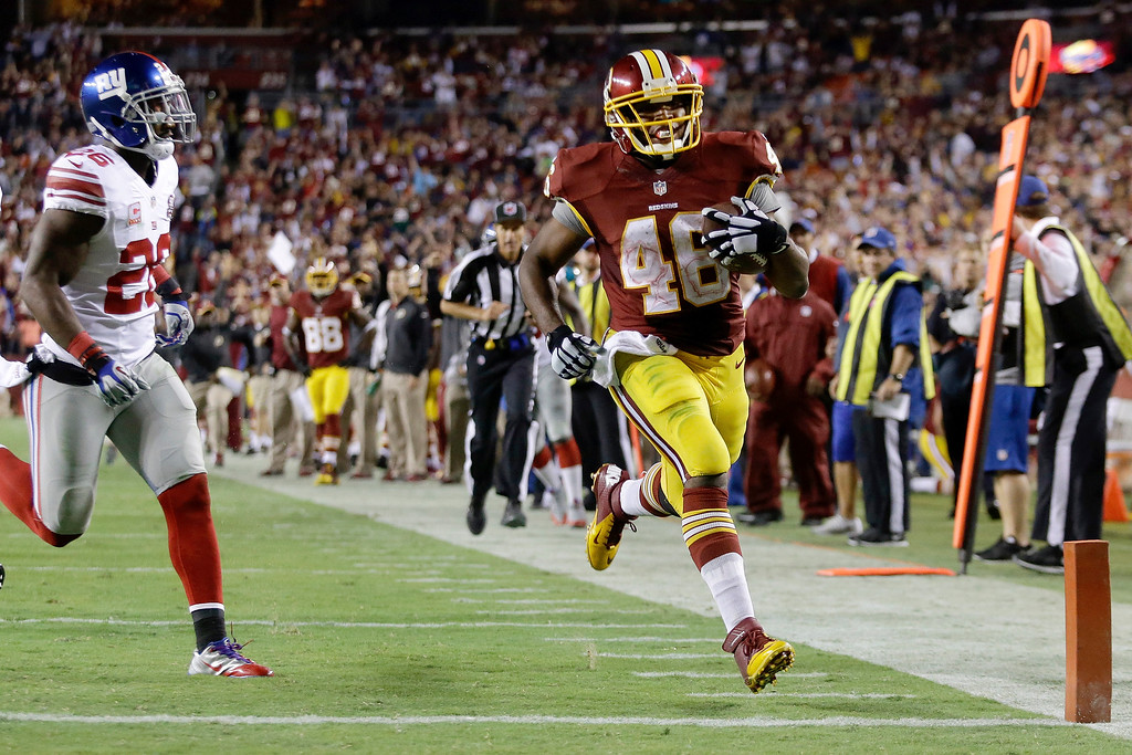 . Washington Redskins running back Alfred Morris (46) steps into the end zone for a touchdown as New York Giants strong safety Antrel Rolle (26) pursues during the second half of an NFL football game in Landover, Md., Thursday, Sept. 25, 2014. (AP Photo/Patrick Semansky)