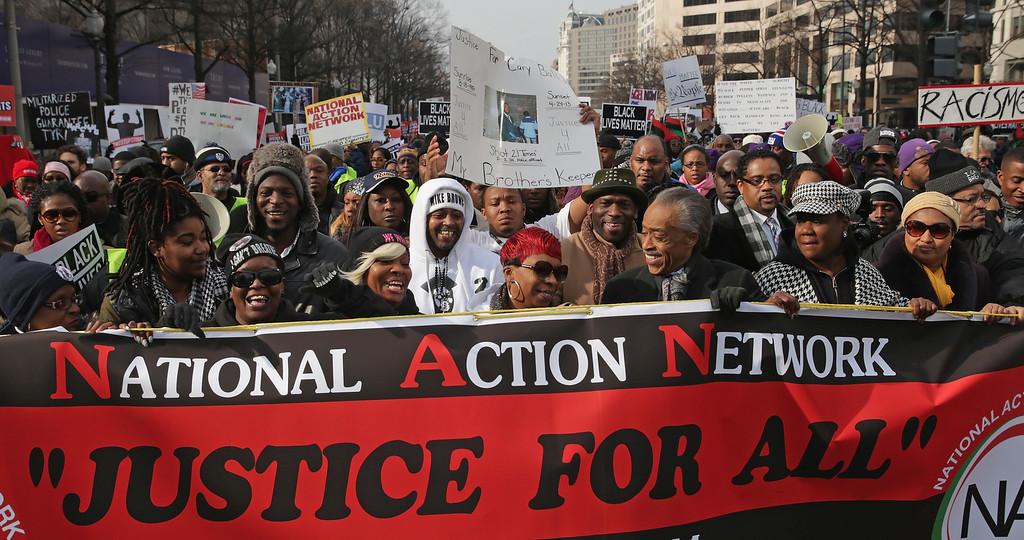 ". Rev. Al Sharpton (C) leads the ""Justice For All\"" march  in the nation\'s capital with the families of Eric Garner, Michael Brown, Tamir Rice, Trayvon Martin, Amadou Diallo and other unarmed black men who were killed by police, December 13, 2014 in Washington, DC. Organized Sharpton\'s National Action Network, this march and other like it across the country aim to tell Congress and the country that demonstrators will not stand down until there is systemic change, accountability and justice in cases of police misconduct. Sharpton said the demonstration is happening in Washington \""because all over the country we all need to come together and demand this Congress deal with the issues, that we need laws to protect the citizens in these states from these state grand jurors.\""  (Photo by Chip Somodevilla/Getty Images)"
