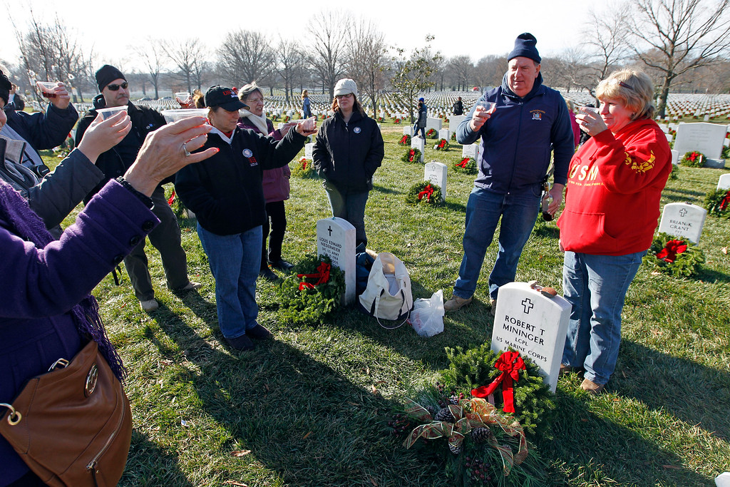 . Paula Zwillinger right, makes a toast with friends over the grave of her son Marine Lance Cpl. Robert T. Mininger  as volunteers lay wreaths at each grave at Arlington National Cemetery in Arlington, Va., Saturday, Dec. 15, 2012, during Wreaths Across America Day. Wreaths Across America was started in 1992 at Arlington National Cemetery by Maine businessman Morrill Worcester and has expanded to hundreds of veterans\' cemeteries and other locations in all 50 states and beyond. (AP Photo/Jose Luis Magana)