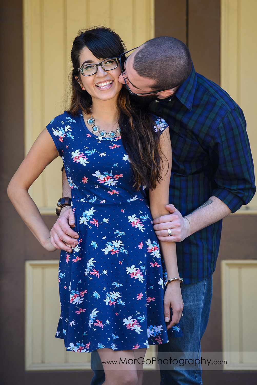 3/4 portrait of man in blue shirt kissing woman in blue dress looking into camera during engagement session at Sunol Station of Niles Canyon Railway