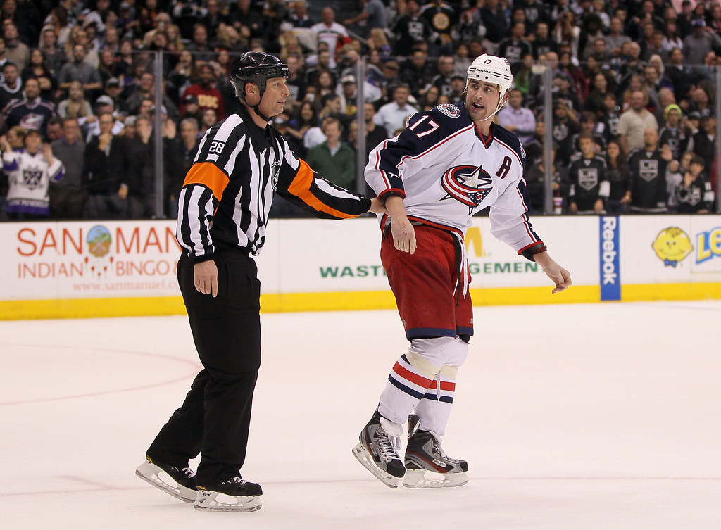 . LOS ANGELES, CA - APRIL 18:  NHL refereee Chris Lee #28 escorts Brandon Dubinsky #17 of the Columbus Blue Jackets toward the Blue Jackets bench after a scrum against the Los Angeles Kings at the end of the third period of their NHL game at Staples Center on April 18, 2013 in Los Angeles, California. The Kings defeated the Blue Jackets 2-1.  (Photo by Victor Decolongon/Getty Images)