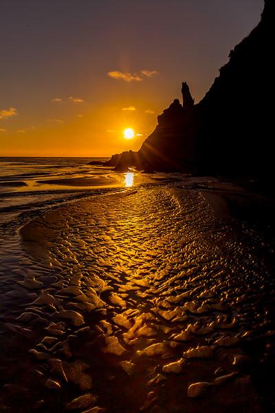 Goldener Sand beim Sonnenuntergang an der Piha Beach