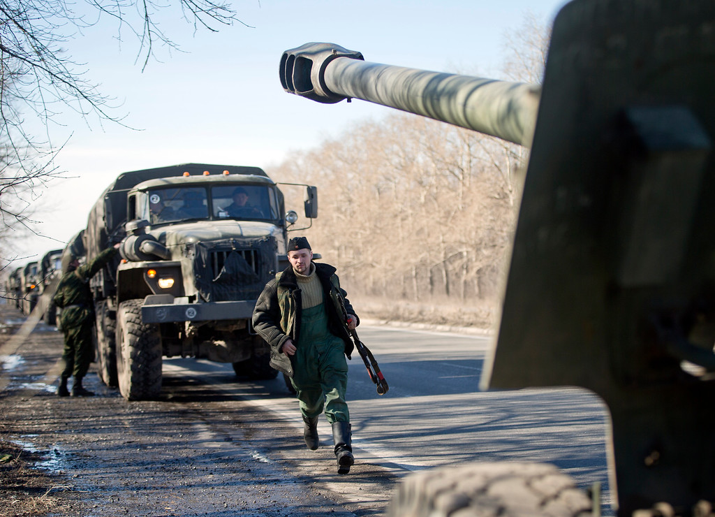 . A Russia-backed separatist fighter runs to his vehicle as a convoy transporting artillery pieces  outside the city of Donetsk, Ukraine,Tuesday, Feb. 24, 2015. Howitzers were seen moving east Tuesday from the largest rebel-held city in eastern Ukraine further into separatist-controlled territory, but the Ukrainian government disputed the rebels\' claim that a heavy weapons pullback had begun.(AP Photo/Vadim Ghirda)