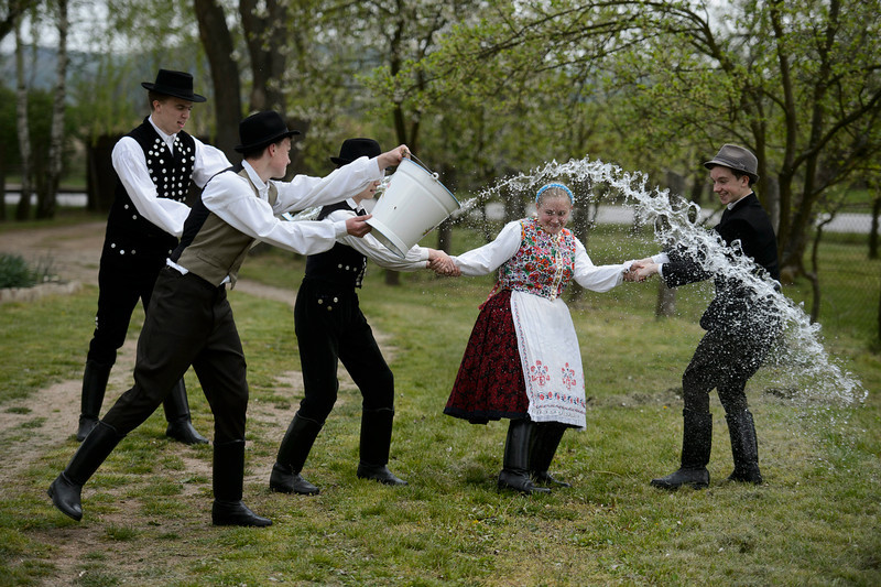 . Young men dressed in traditional Paloc folk costumes pour water from a bucket on a young woman performing an Easter folk tradition, the Easter sprinkling, in Kazar, some 100 kilometers northeast of Budapest, Hungary, Good Friday, April 18, 2014. (AP Photo/MTI, Peter Komka)