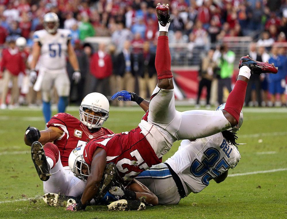 Description of . Arizona Cardinals' William Gay (22) tackles Detroit Lions' Joique Bell (35) as Cardinals' Paris Lenon, left, looks on during the second half of an NFL football game on Sunday Dec. 16, 2012, in Glendale, Ariz.  The Cardinals defeated the Lions 38-10. (AP Photo/Ross D. Franklin)