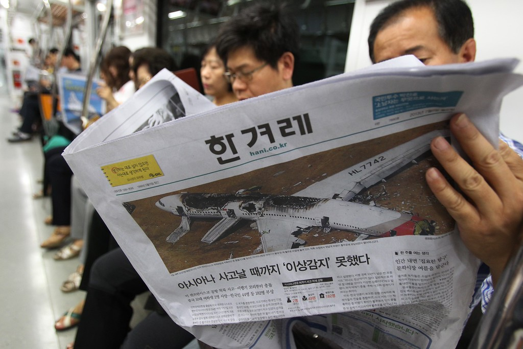 """. A passenger reads a newspaper reporting about Asiana Airlines flight 214 which took off from Seoul and crashed while landing at San Francisco International Airport  on Saturday, on a subway train in Seoul, South Korea, Monday, July 8, 2013.  The headline reads \""""Asiana did not notice anything wrong until the accident happened.\"""" (AP Photo/Ahn Young-joon)"""