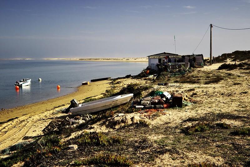 Poslední budovy na Ilha de Faro. Tady končí i dřevěná stezka, dál už je jen písek. Ostrov ještě asi kilometr pokračuje, aby byl následně přerušen úzkým přirozeným průlivem. Poté pokračuje dál, ale už jako Ilha Deserta, neboli Opuštěný ostrov, na který se dá dostat jedině lodí.