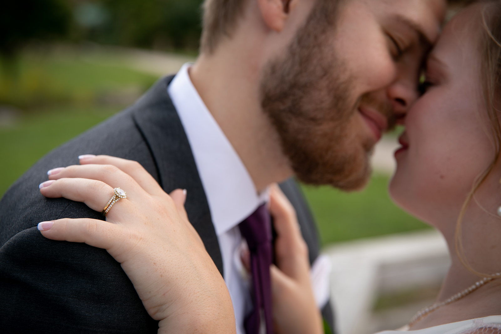 A close up photograph of a bride's engagement ring with the bride and groom holding each other in the blurred background