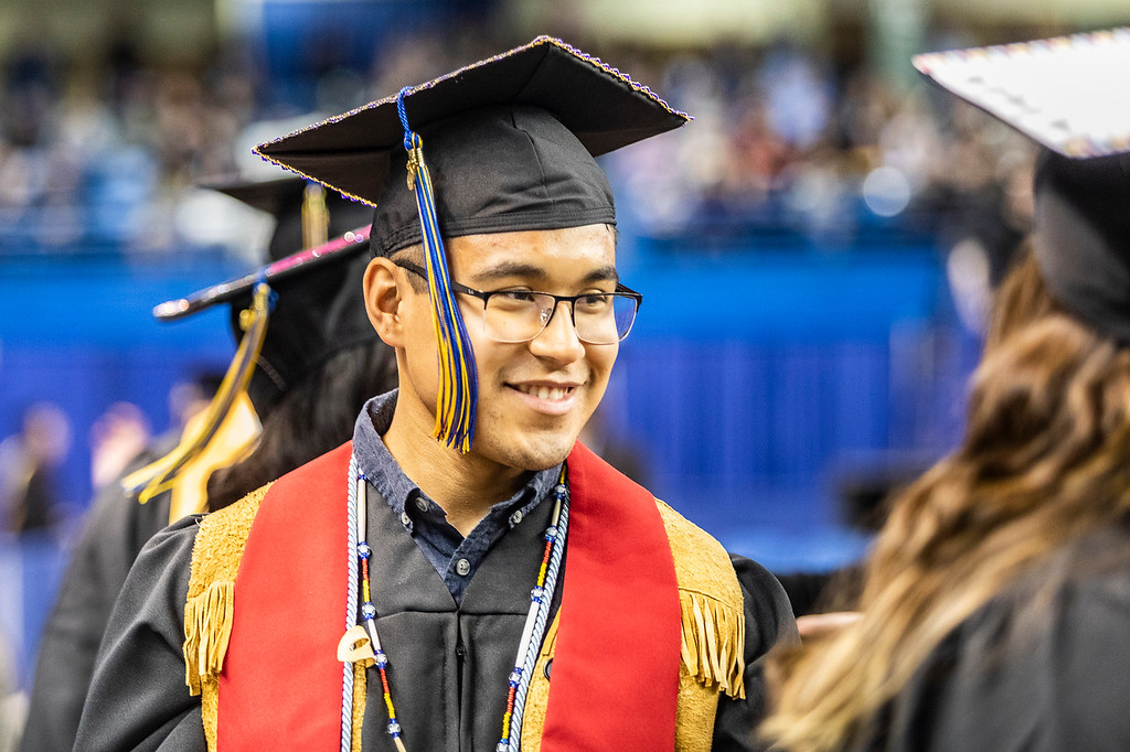 Joe Bifelt smiles as he walks to his seat at the UAF 2019 commencement ceremony at the Carlson Center.