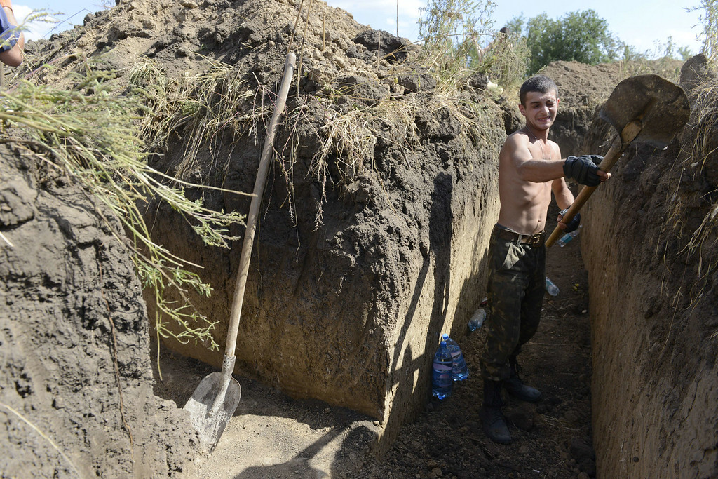 """. An Ukrainian soldier digs a trench on the outskirts of the southern Ukrainian city of Mariupol  on August 29, 2014. NATO chief Anders Fogh Rasmussen urged Russia on August 29 to halt its \""""illegal\"""" military actions in Ukraine, accusing it of a \""""dangerous\"""" attempt to destabilise its western neighbour. The conflict raging in eastern Ukraine has killed nearly 2,600 people, the United Nations said on August 29, voicing concern about atrocities committed by armed groups and the increasing involvement of foreign fighters. Alexander KHUDOTEPLY/AFP/Getty Images"""