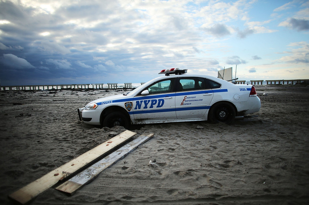 . An abandoned police car is viewed on the heavily damaged beach in the Rockaway section of Brooklyn after Hurricane Sandy on October 31, 2012 in the Queens borough of New York City. With the death toll currently at 55 and millions of homes and businesses without power, the US East Coast is attempting to recover from the affects of floods, fires and power outages brought on by Hurricane Sandy. JFK airport in New York and Newark airport in New Jersey expect to resume flights on Wednesday morning and the New York Stock Exchange commenced trading after being closed for two days.  (Photo by Spencer Platt/Getty Images)