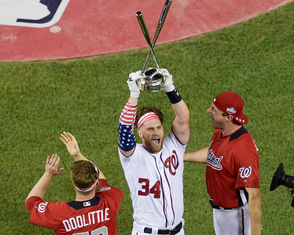 . Washington Nationals Bryce Harper holds up the trophy after winning the the Major League Baseball Home Run Derby Monday, July 16, 2018, in Washington. (AP Photo/Susan Walsh)
