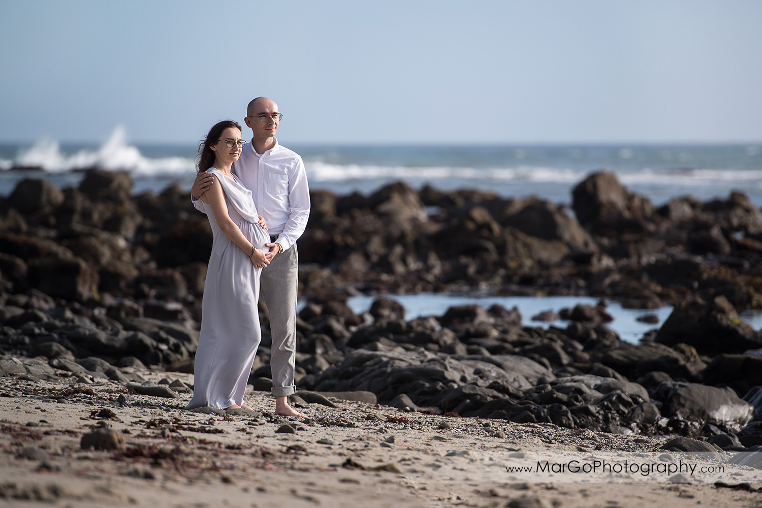 full body portrait of man and pregnant woman in gray dress standing on the Moss Beach during maternity session