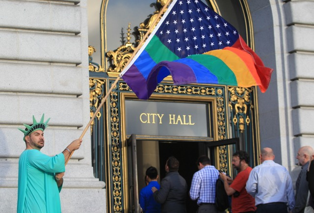 . Nikolas Lemos, of San Francisco waves a rainbow flag in front of San Franciaco City Hall while awaiting the Supreme Court\'s Proposition 8 ruling in San Francisco, Calif., on Wednesday, June 26, 2013. (Jane Tyska/Bay Area News Group)