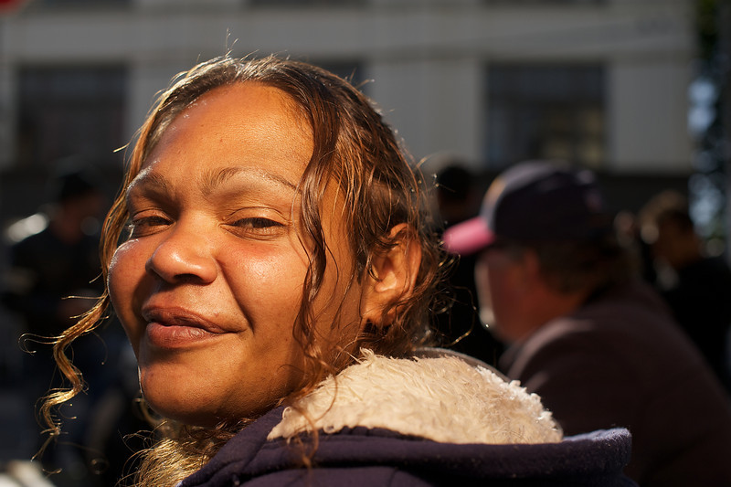 Aboriginal Woman of twenty-eight looking over her shoulder at camera.  There is golden evening light on her face.
