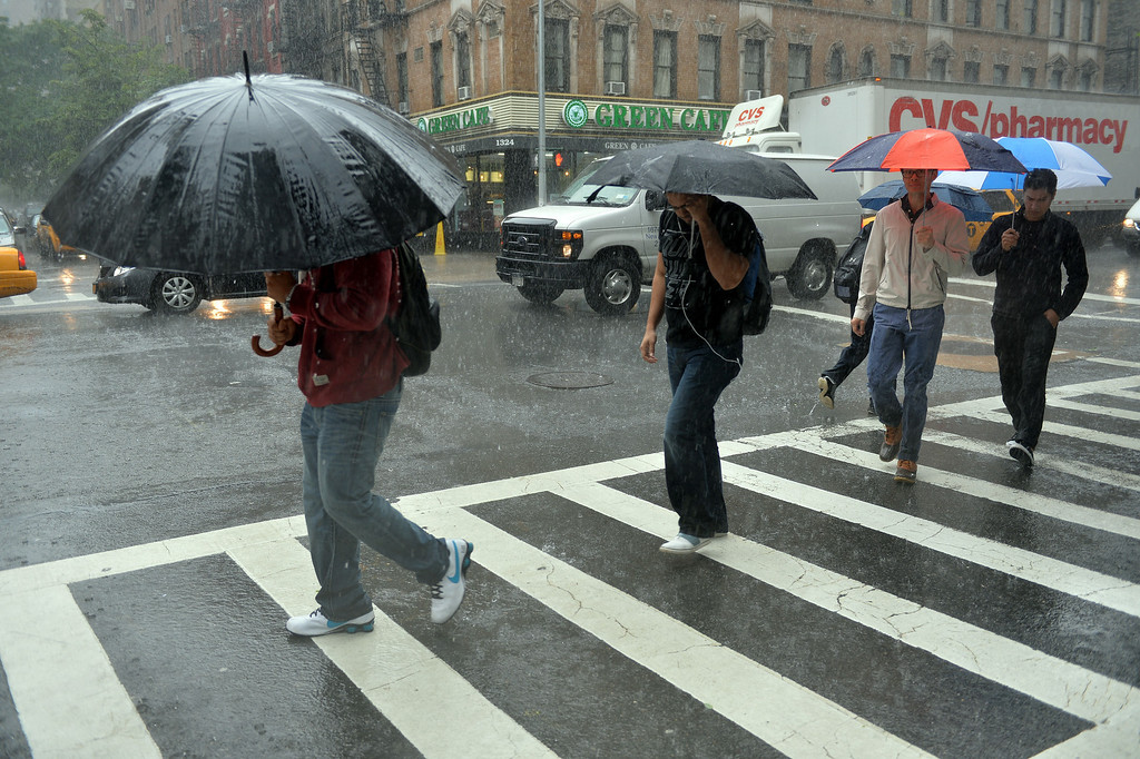 . People on Lexington Avenue cross East 88th Street in a downpour June 13, 2013 in New York as a severe storm affects the northeasten US. AFP PHOTO/Stan  HONDA/AFP/Getty Images